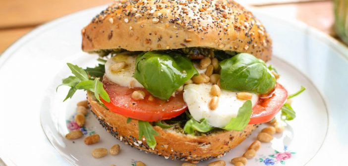 Een zomers broodje Caprese met mozzarella, tomaat, basilicum, rucola en pijnboompitten